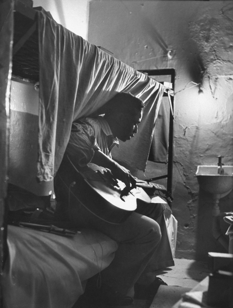 "Robert Riley, serving 10 to 16 years for housebreaking, sits in his cell composing music, Tennessee State Penitentiary, 1953. Riley co-wrote the hit song, ""Just Walkin' in the Rain."""