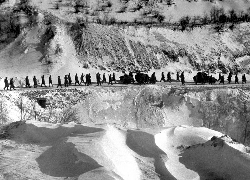 "A column of American Marines marches down a canyon road dubbed ""Nightmare Alley"" during their retreat from Chosin Reservoir, Korea, 1950."