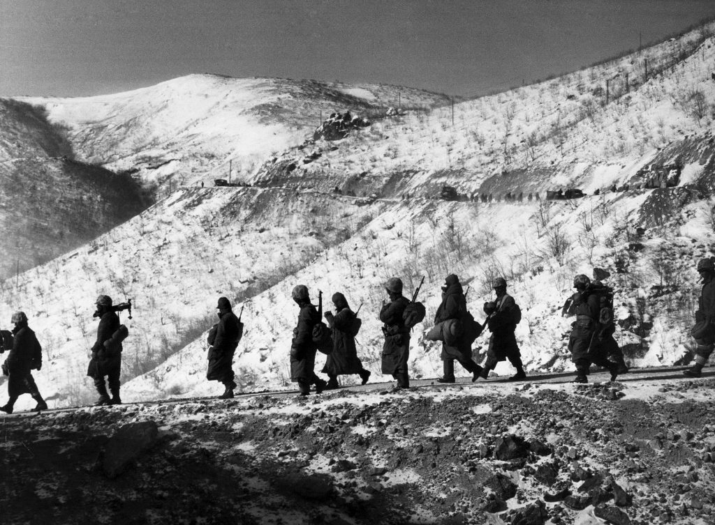 "American Marines march down a canyon road dubbed ""Nightmare Alley"" during their retreat from Chosin Reservoir, Korea, 1950."