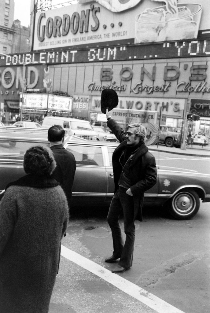 Robert Redford hails a cab in Times Square