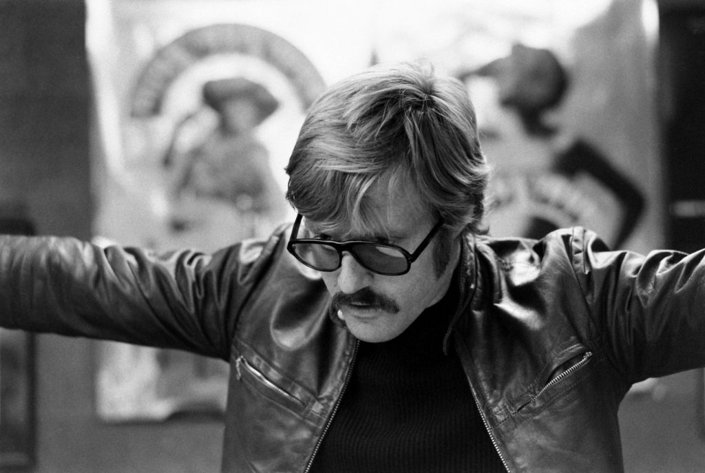 """Robert Redford looks over promotional photos and ads for """"Downhill Racer"""""""