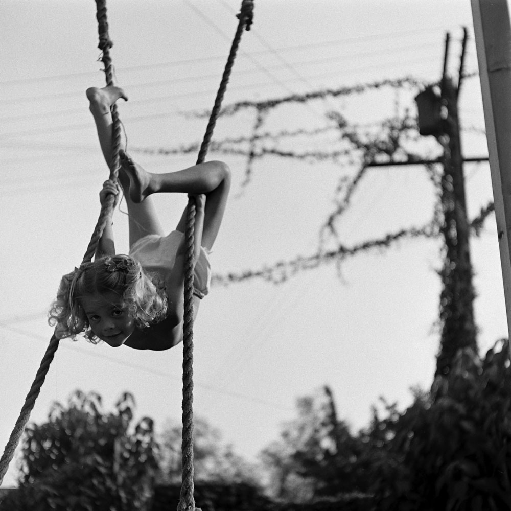 Natalie Wood swings upside down in her backyard as a child