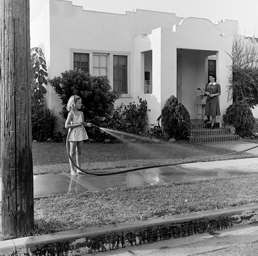 Natalie Woods waters the lawn as her mother, Maria Gurdin, supervises