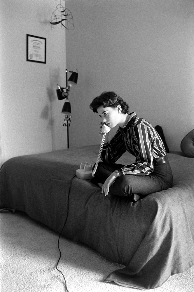 Natalie Wood takes a call while sitting on her bed at home in 1965.
