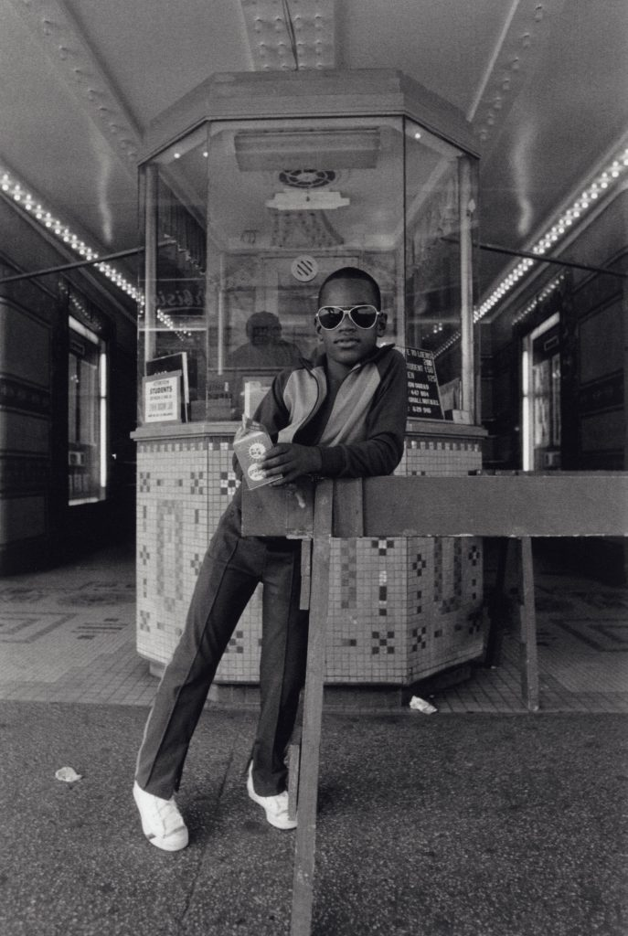 A boy in front of the Loews 125th Street movie theater, 1976.