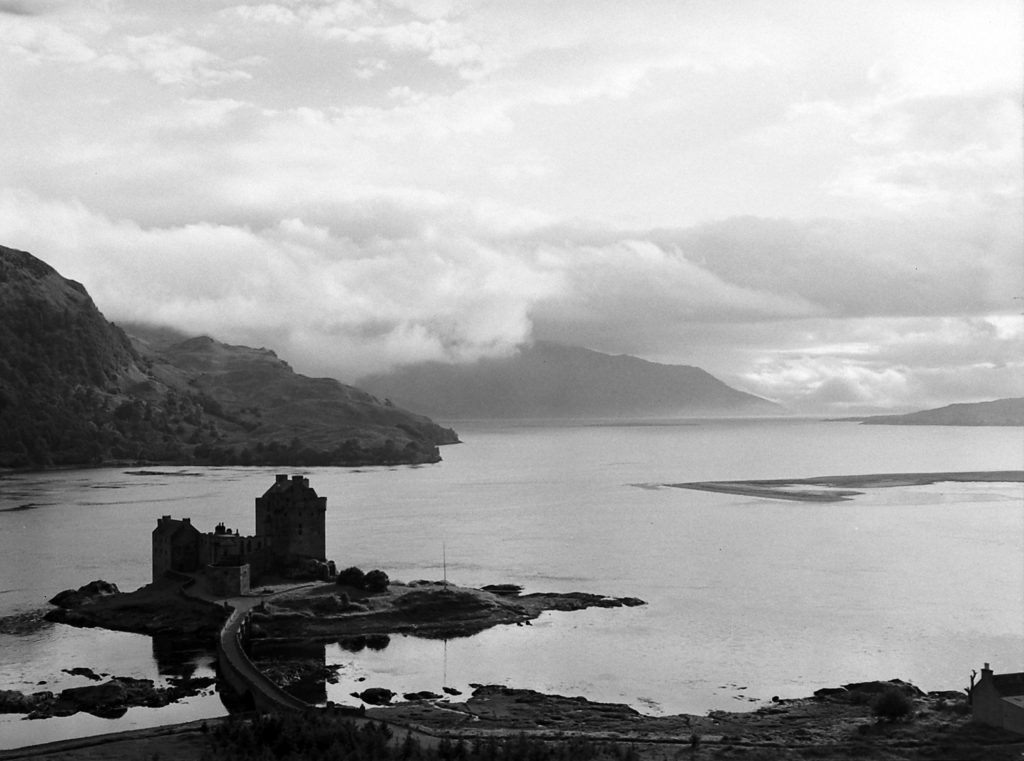 Eilean Donan Castle guards Loch Duich in the western Highlands near Dornie. Under the low cloud (right) lies the Isle of Skye to which Prince Charlie once fled, disguised as the serving maid of Scottish Heroine Flora Macdonald. The castle was wrecked by British gunfire in 1719 when it was a headquarters for Spanish and Scottish leaders in one of the endless revolts against the English crown. This land once was prowled by a legendary giant who created islands in nearby lochs by throwing stones.