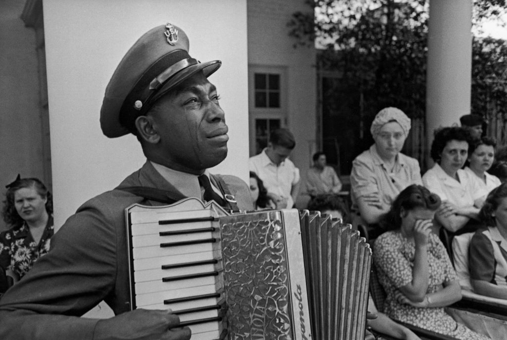 Tears stream down the cheeks of accordion-playing Chief Petty Officer (USN) Graham Jackson as President Franklin D. Roosevelt's flag-draped funeral train leaves Warm Springs, Ga., April 13, 1945.