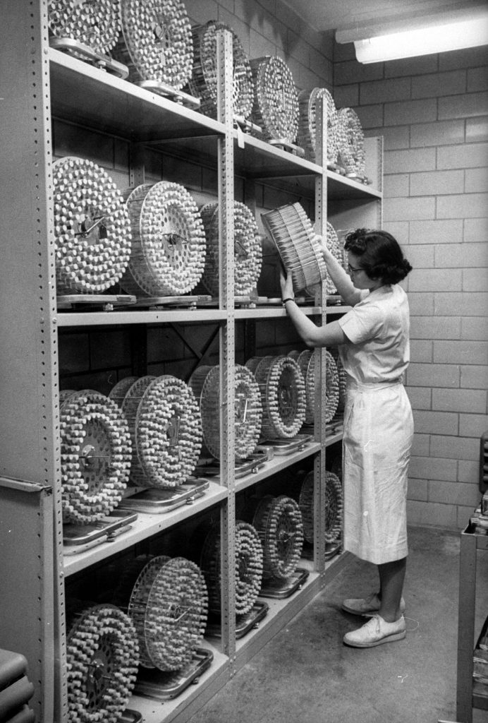 In incubator room, test tubes of vaccine samples rotate slowly in drums for seven days under controlled temperature. The samples are then analyzed.