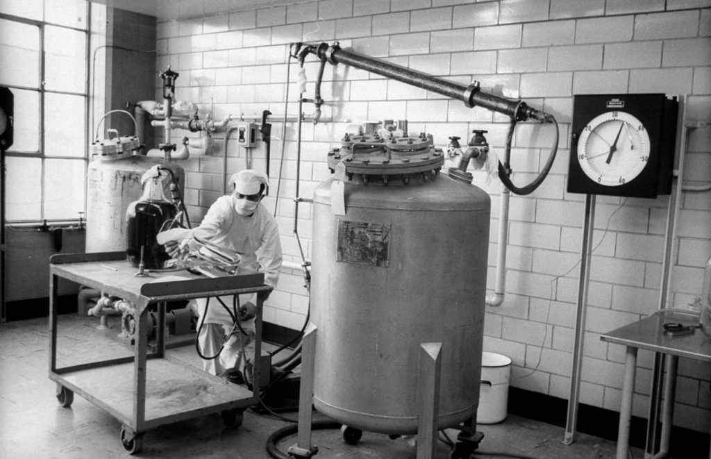 To kill virus, worker makes up formaldehyde solution which is pumped into tube overhead simultaneously with vaccine-to-be from tank. When throughly mixed, liquid goes back into tank where formaldehyde does its work.