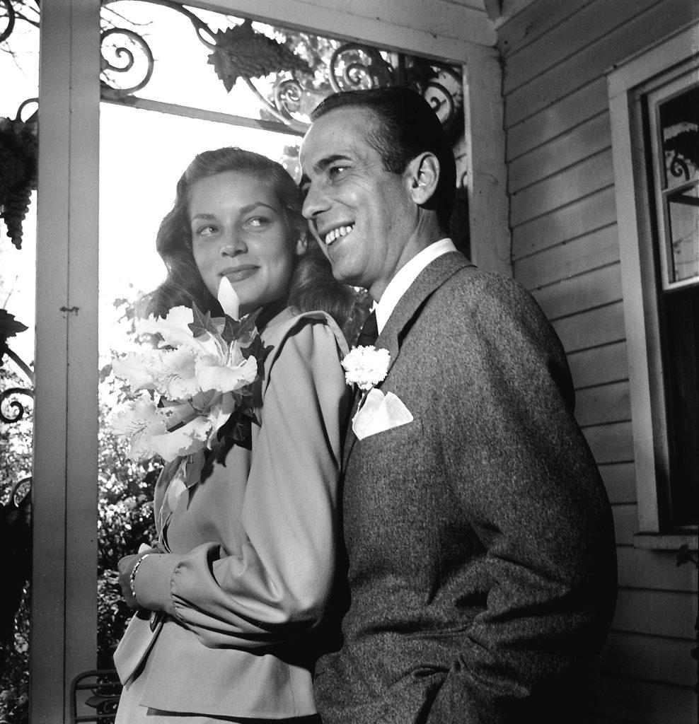 Newlywed actors Humphrey Bogart and Lauren Bacall attending wedding reception at the home of novelist Louis Bromfeld.