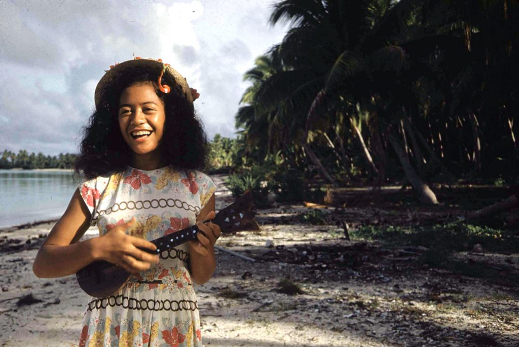 A Tahitian woman playing the Ukelele.