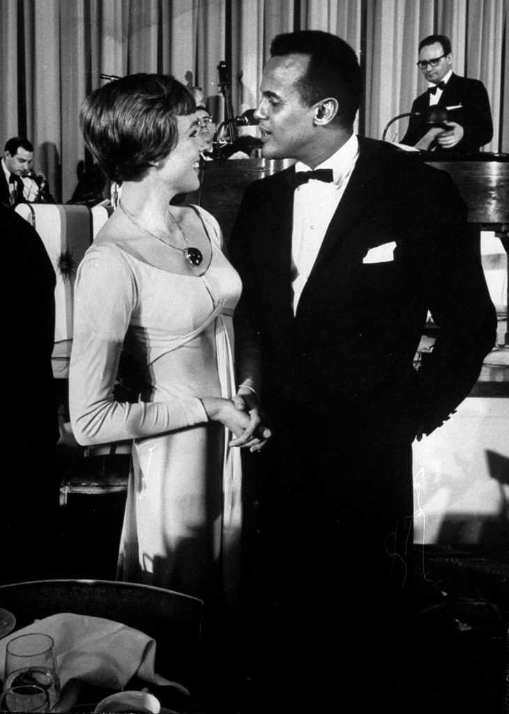 Singer Harry Belafonte with Julie Andrews at party following Broadway premiere of 'Sound of Music'.