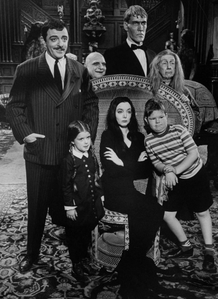Carolyn Jones and John Astin, with other cast members, from The Addams Family.