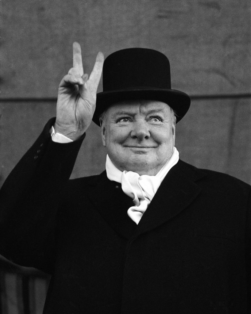 British PM Winston Churchill sporting top hat with coat and scarf.