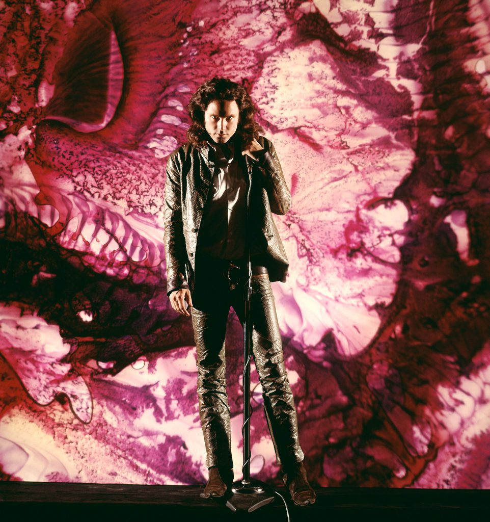 Jim Morrison of The Doors wearing leather and singing alone on stage in front of a purple psychedelic backdrop.