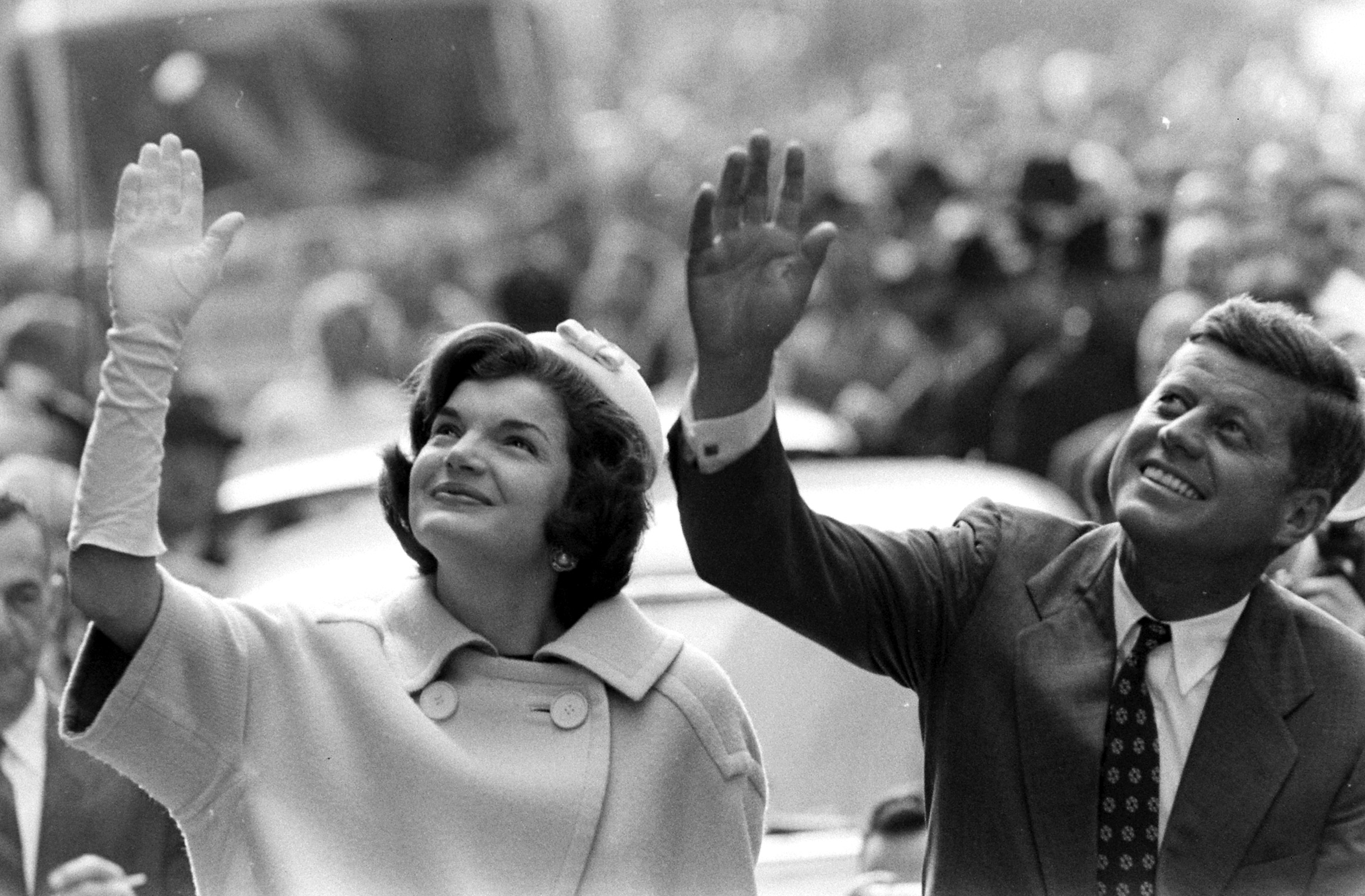 John F. Kennedy and wife Jackie waving to a crowd during campaign appearance.