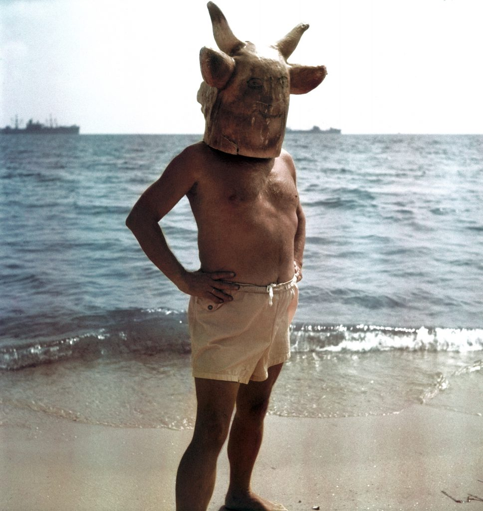 Pablo Picasso wearing a minotaur head mask on the beach at Golfe Juan near Vallauris.