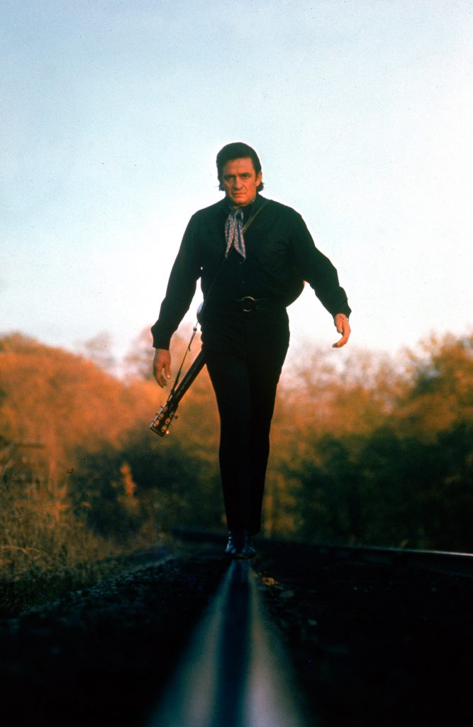 Country music star Johnny Cash walking along the line of a railway track.