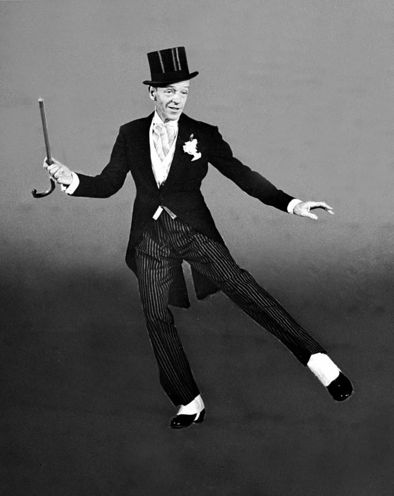 "Dancer Fred Astaire clad in top hat, tails and spats, twirling cane in one hand as he dances ""Puttin' on the Ritz"" number for the movie ""Blue Skies.""."