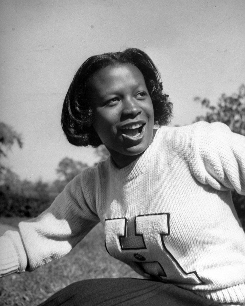 Howard University cheerleader Alfreda Young leading cheer during football game, 1946.