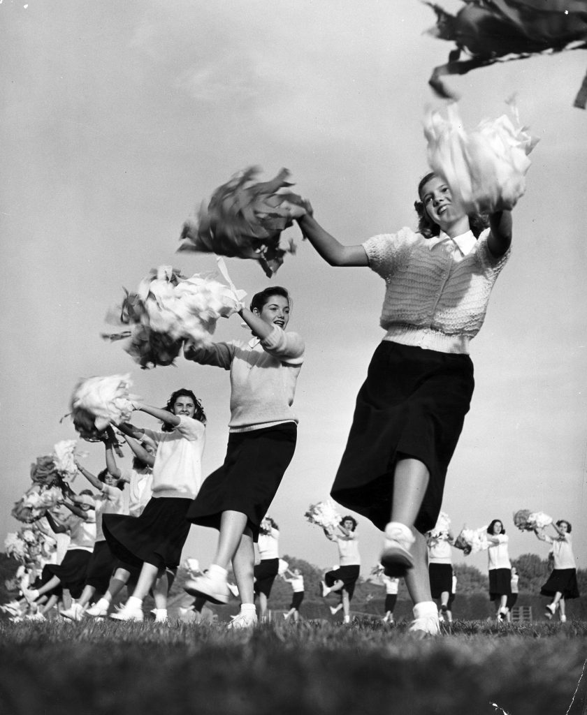 Sixty high school cheerleaders with crepe-paper pompons whip up football spirit, 1947.