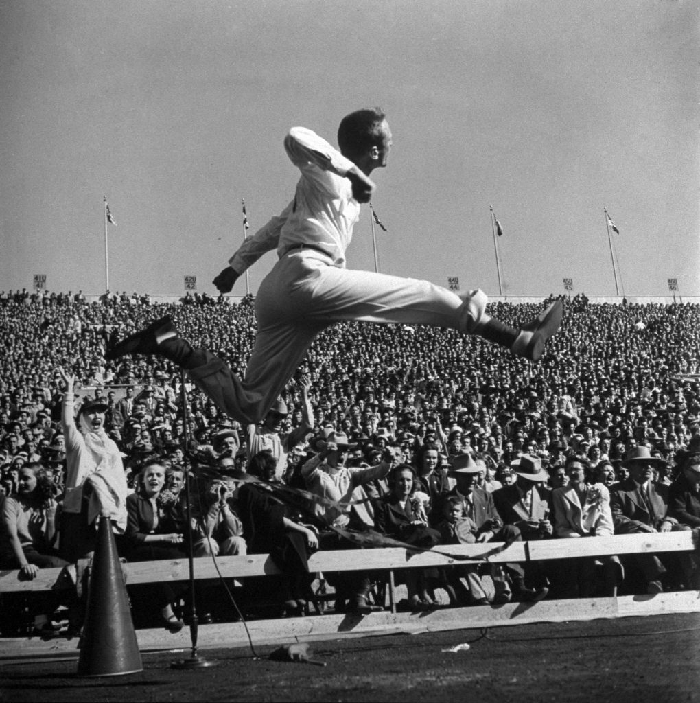 SMU cheerleader leaping high into air at University of Texas football game, 1950.