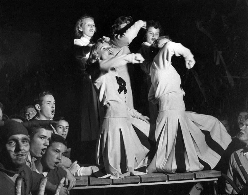 Duke cheerleaders cheering among the fans in the bleachers, 1952.