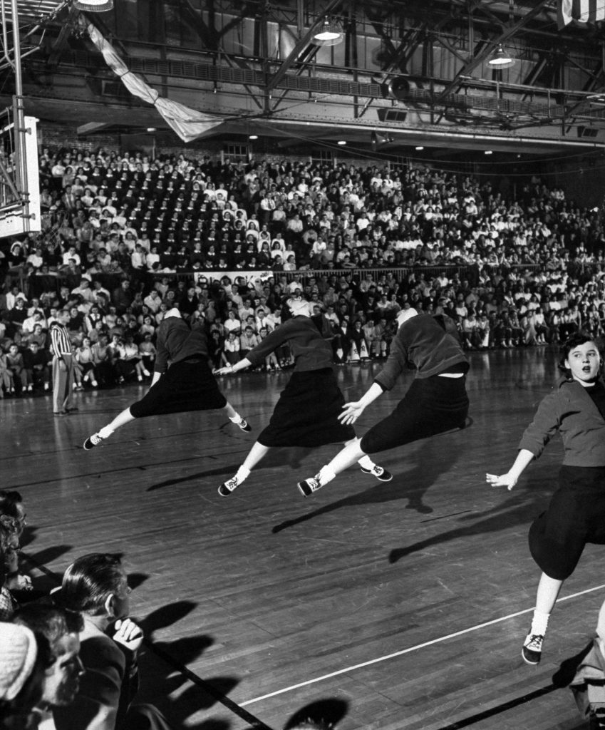 High school girl cheerleaders wearing sweaters and skirts leaping high in the air during their vigorous cheers at the basketball game, 1953.