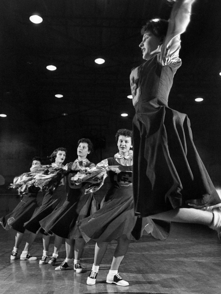 The girls of Central Catholic High School performing their cheerleading act in the gym, 1953.