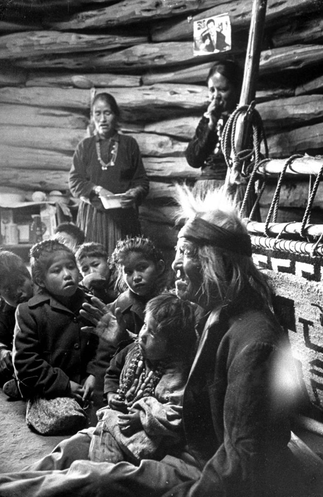 Seated close to the evening fire, Gray Mountain, 91, tells his grandchildren legends about the early days of the Navajo people.