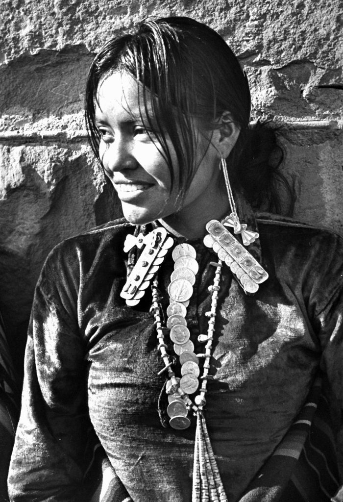 Navajo woman sporting Navajo-crafted silver shirt collar caps, long beaded earrings, beaded necklace complete with silver quarters and 50-cent pieces strung together like a tie.