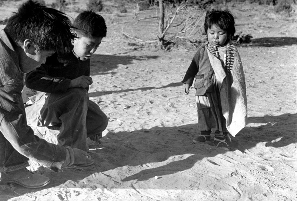 Game of marbles, one popular part of white man's culture, is explained by small boy at center to brother and sister. This boy goes to school and learned the game there. His brother has to stay home to help with the sheepherding.