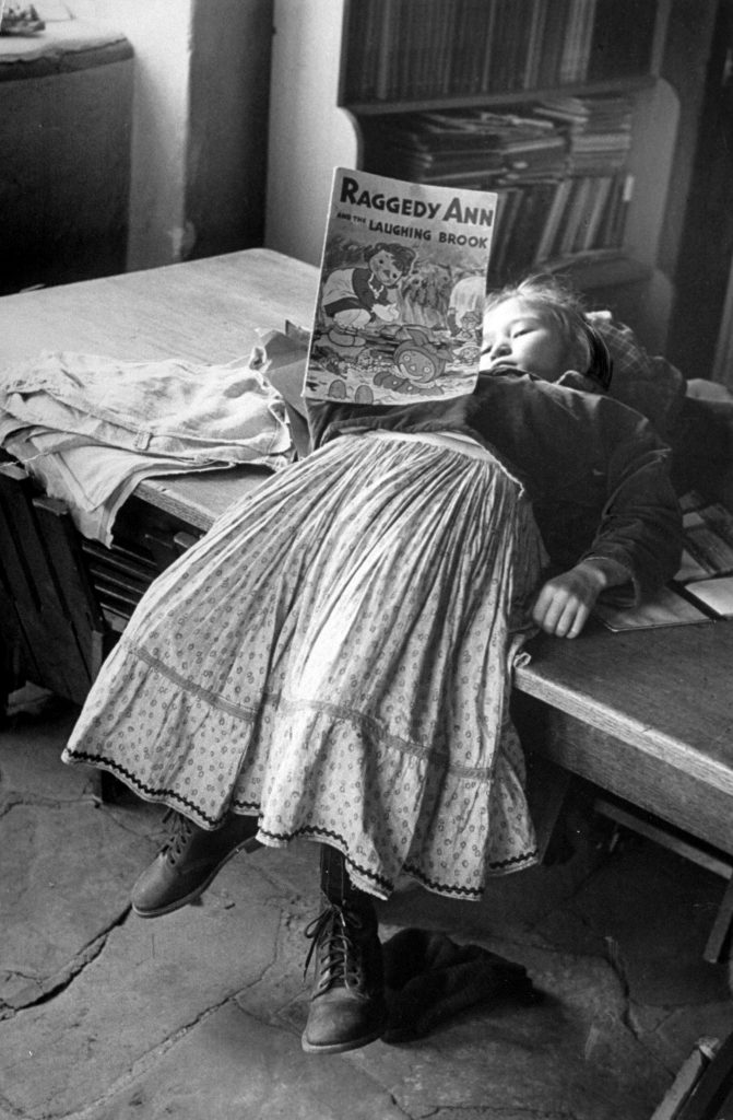 A young Navajo girl reading a Raggedy Ann book.