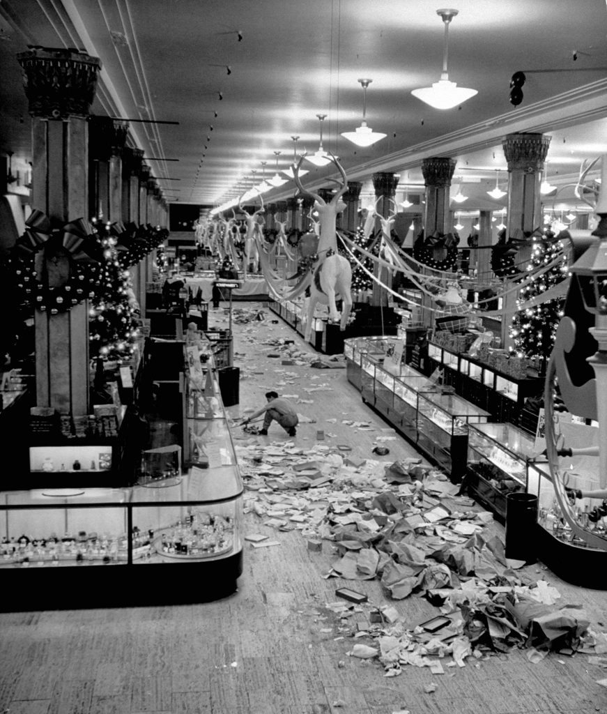 Macy's department store employee cleaning up piles of debris after the Christmas shopping rush, 1948.