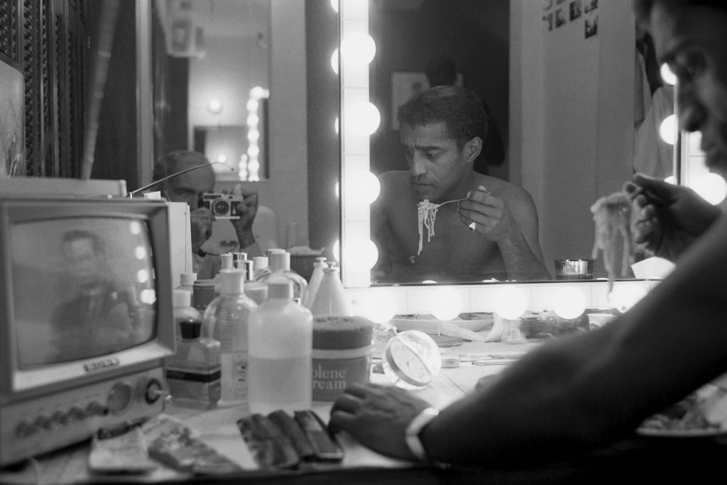 "Sammy Davis Jr. eats spaghetti in his dressing room during ""Golden Boy"", while watching ""The Huntley-Brinkley Report "" (""My only contact with reality,"" he tells LIFE. ""Whatever I'm doing, I stop to watch these guys""). Reflected in the mirror: LIFE photographer Leonard McCombe."