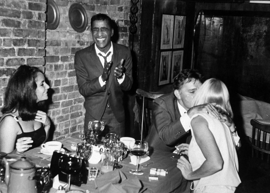 In a New York pub, Sammy applauds as Richard Burton kisses May, Elizabeth beams.