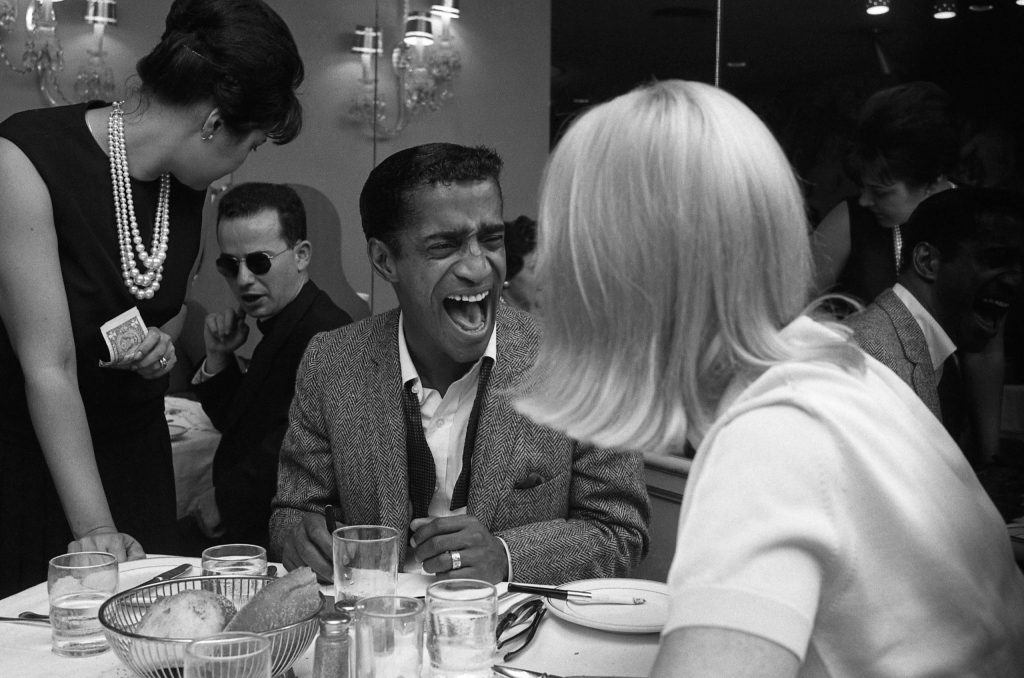 Sammy Davis Jr. laughs over dinner with his then-wife, Swedish actress May Britt.