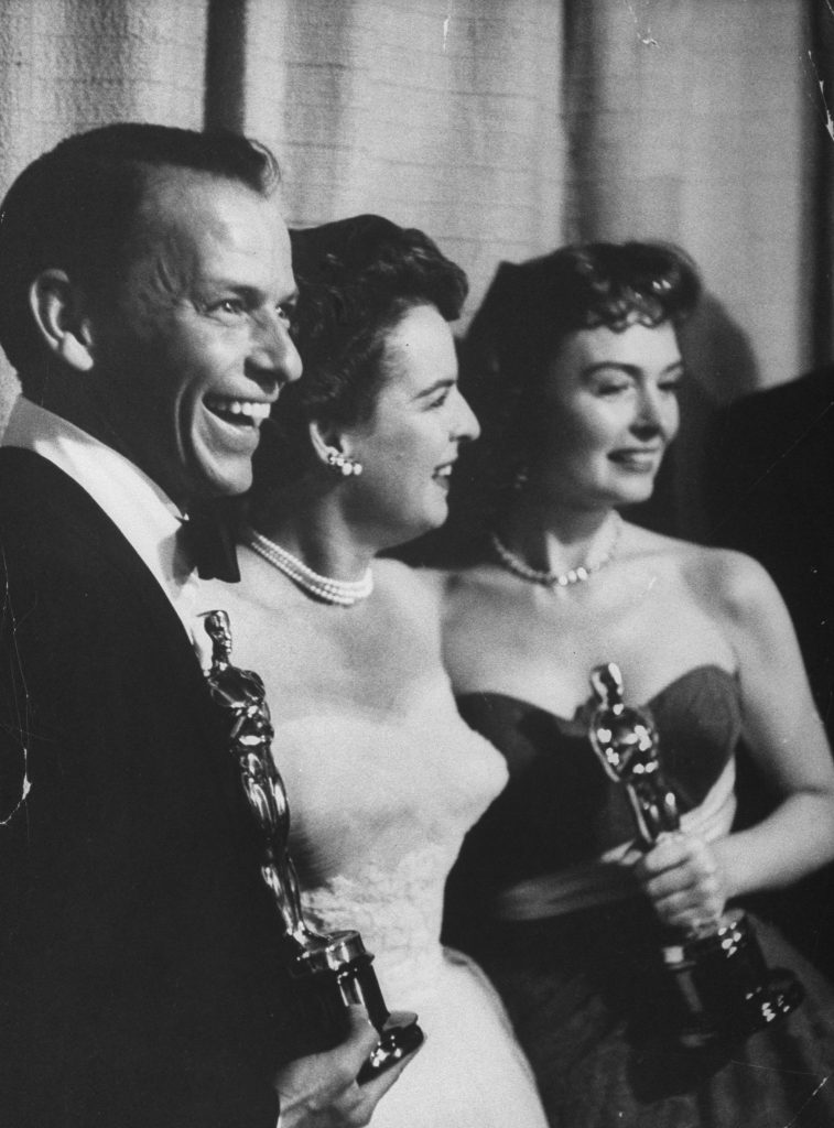 "Frank Sinatra and Donna Reed (R) holding Oscars while posing w. presenter, actress Mercedes McCambridge, for Best Supporting Actors in the movie ""From Here to Eternity"" at the 26th Annual Academy Awards Ceremony, 1954."