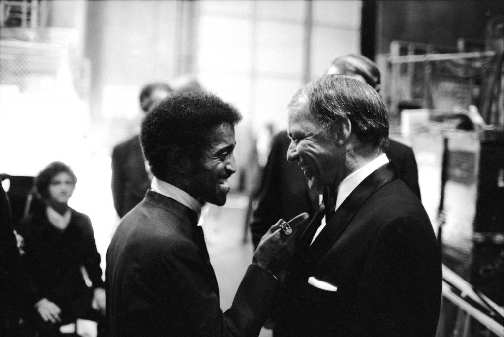 Sammy Davis Jr. talking with singer Frank Sinatra at his farewell peformance, at UCLA, 1971.