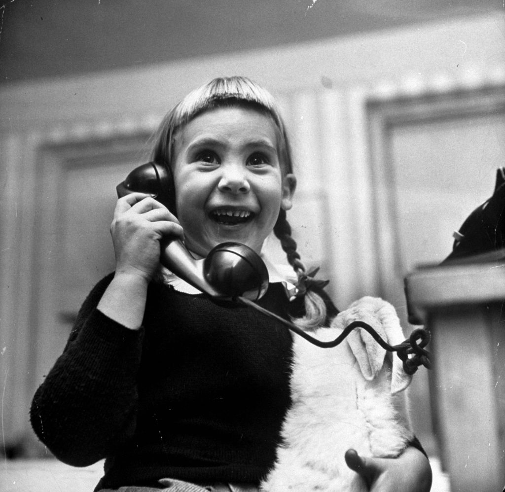 A young girl talking to Santa Claus on the telephone, 1947.