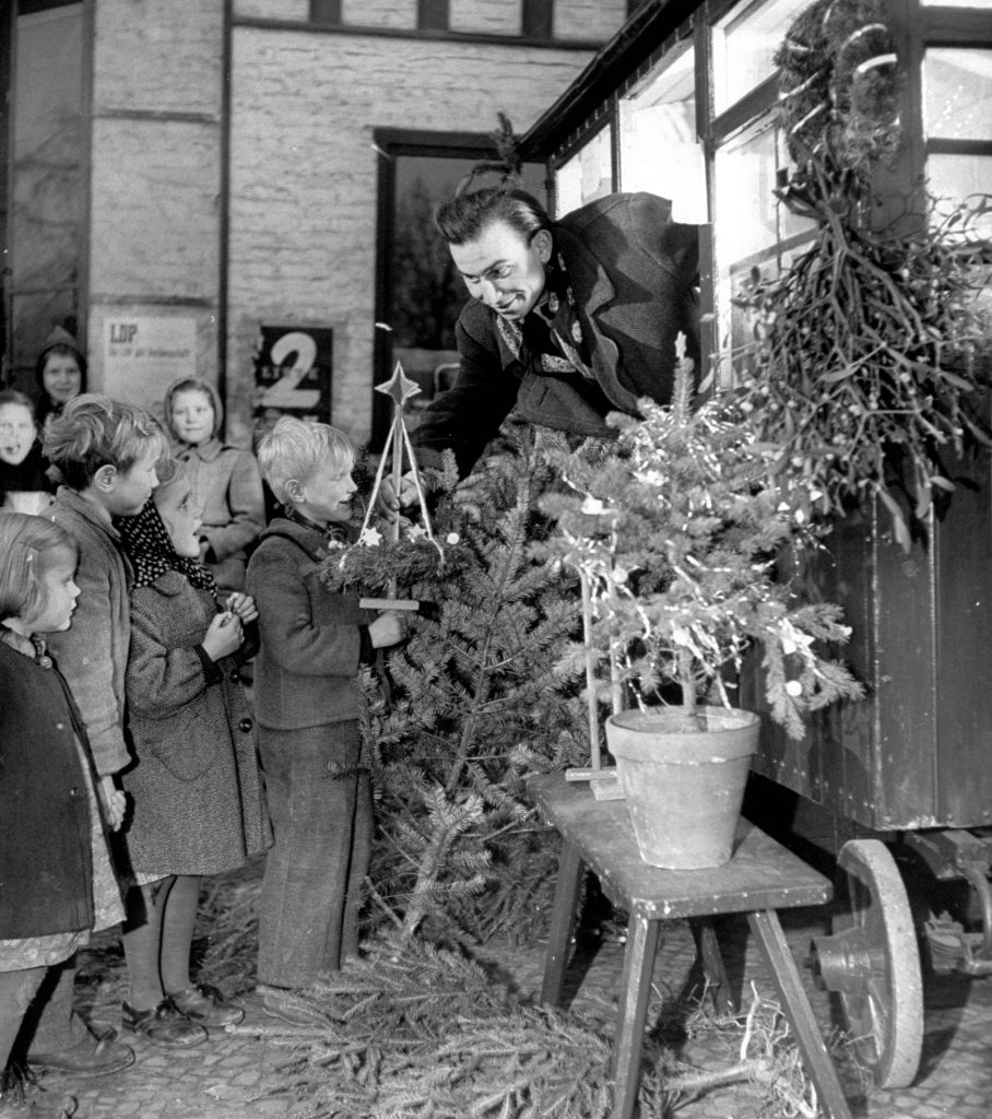 Man showing Christmas decorations to children, 1948.