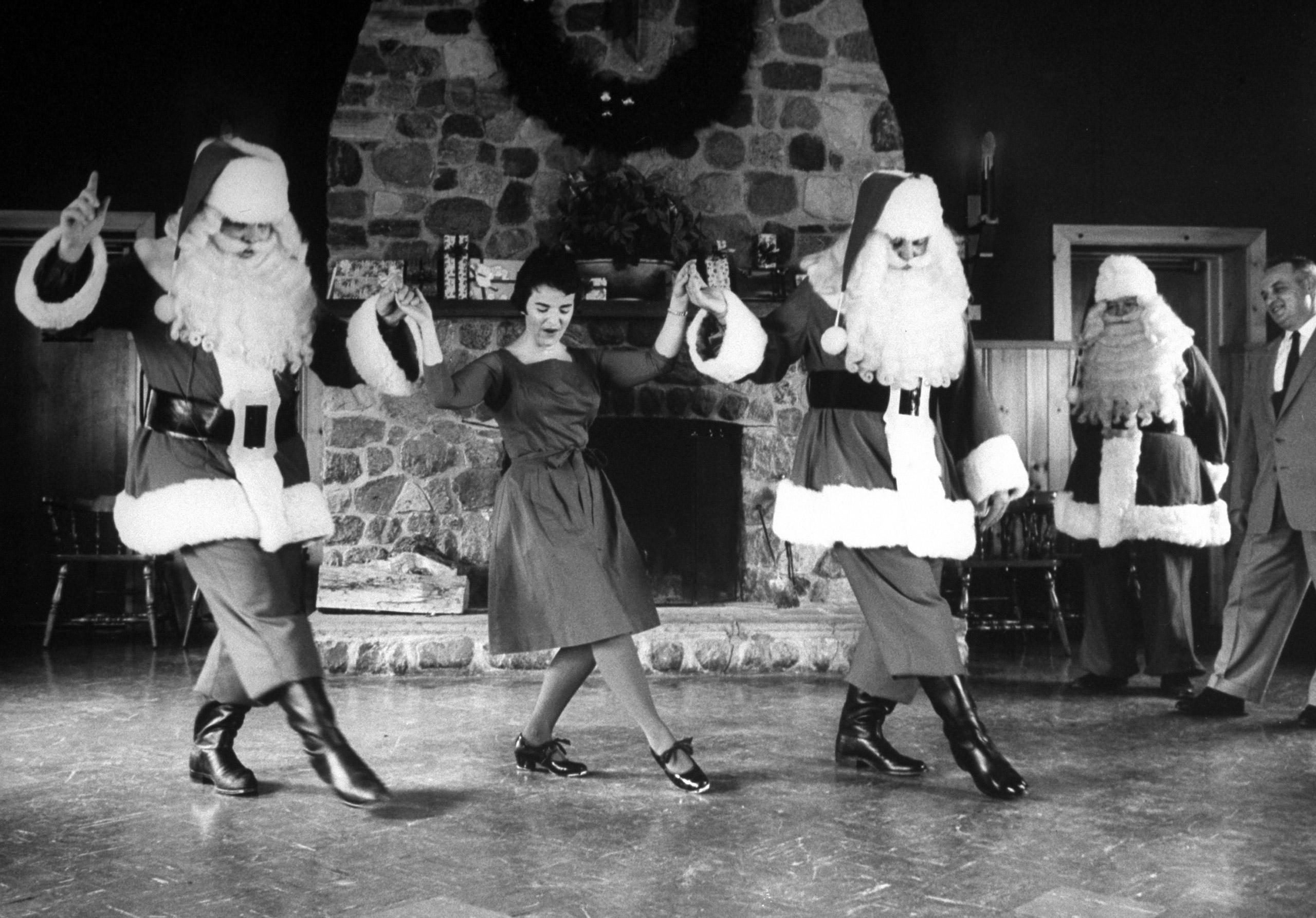 Ken Berends and Bill Burslem practice a soft-shoe with faculty member Joy Merkel in Santa Claus training class at Santa Claus School, 1961.