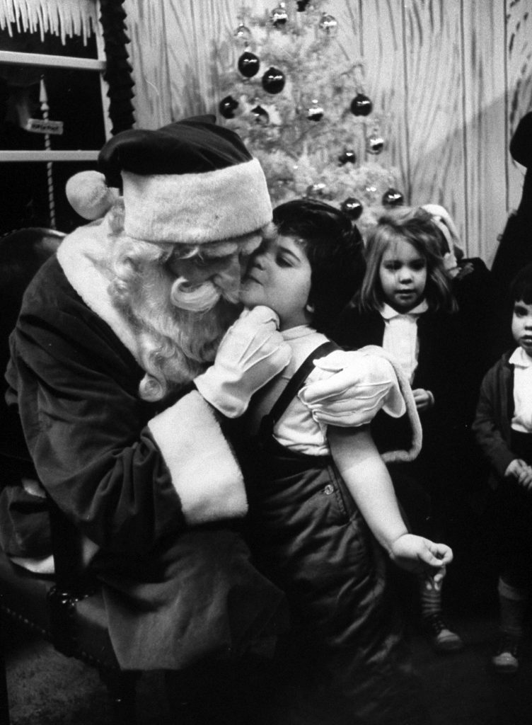 Little girl giving Santa Claus a kiss, 1962.