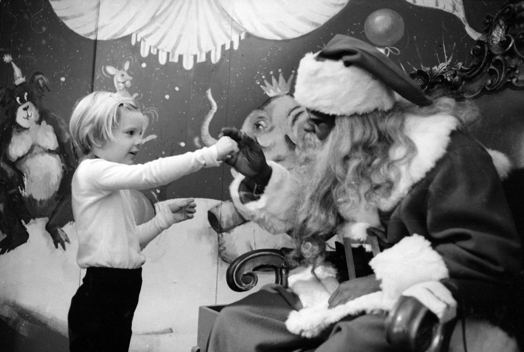 Young child visiting Santa Claus at a department store, 1970.