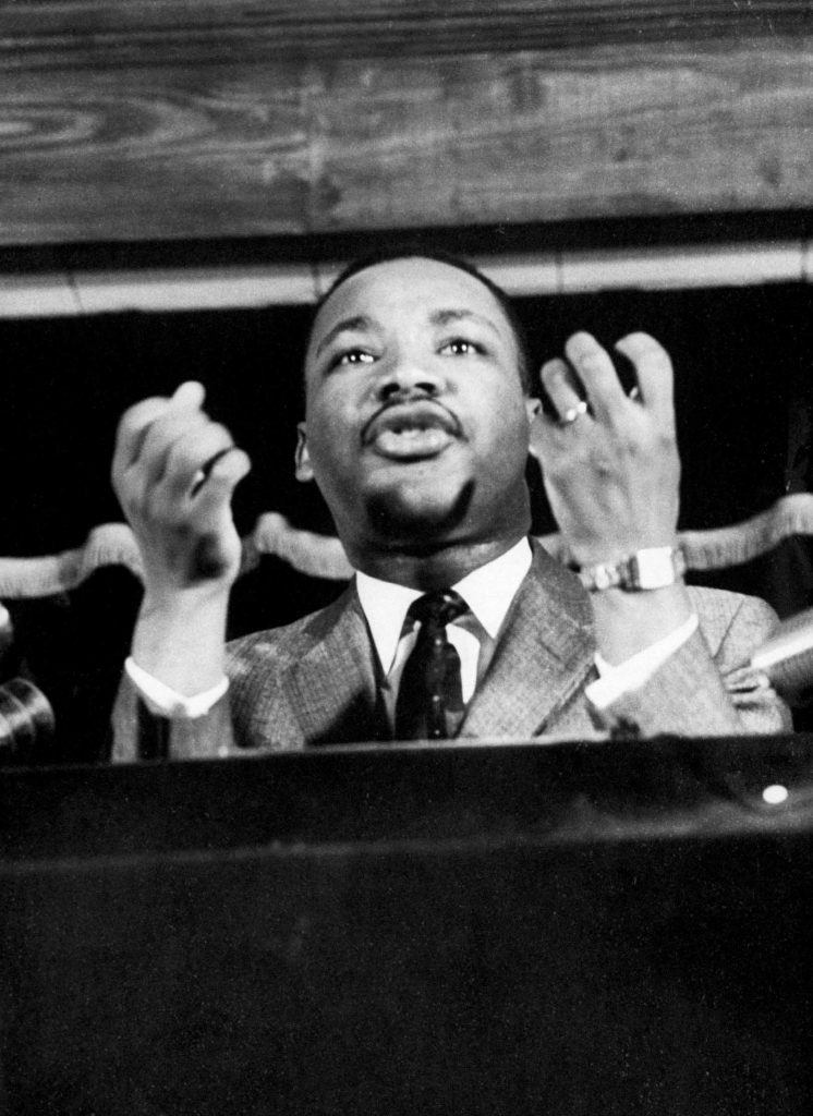 Civil rights leader Rev. Martin Luther King speaking from pulpit at mass meeting about principles of non-violence before leading assembly to ride newly integrated busses after successful boycott.