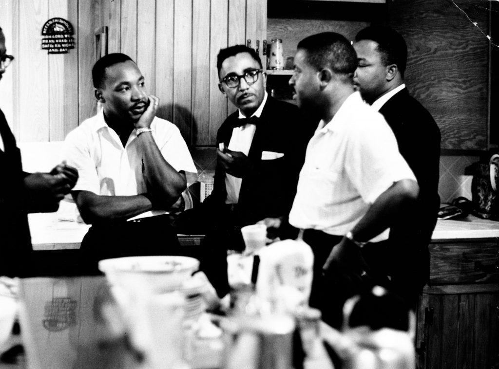 Rev. Martin Luther King Jr. (C) speaking with Rev. Ralph Abernathy (2nd R) and others, 1961.