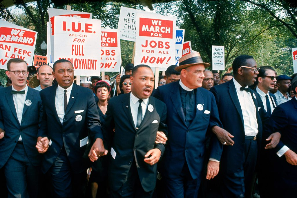 Leaders of March on Washington for Jobs and Freedom marching w. signs (R-L): Matthew Ahmann, Floyd McKissick, Martin Luther King Jr., Rev. Eugene Carson Blake and unidentified.