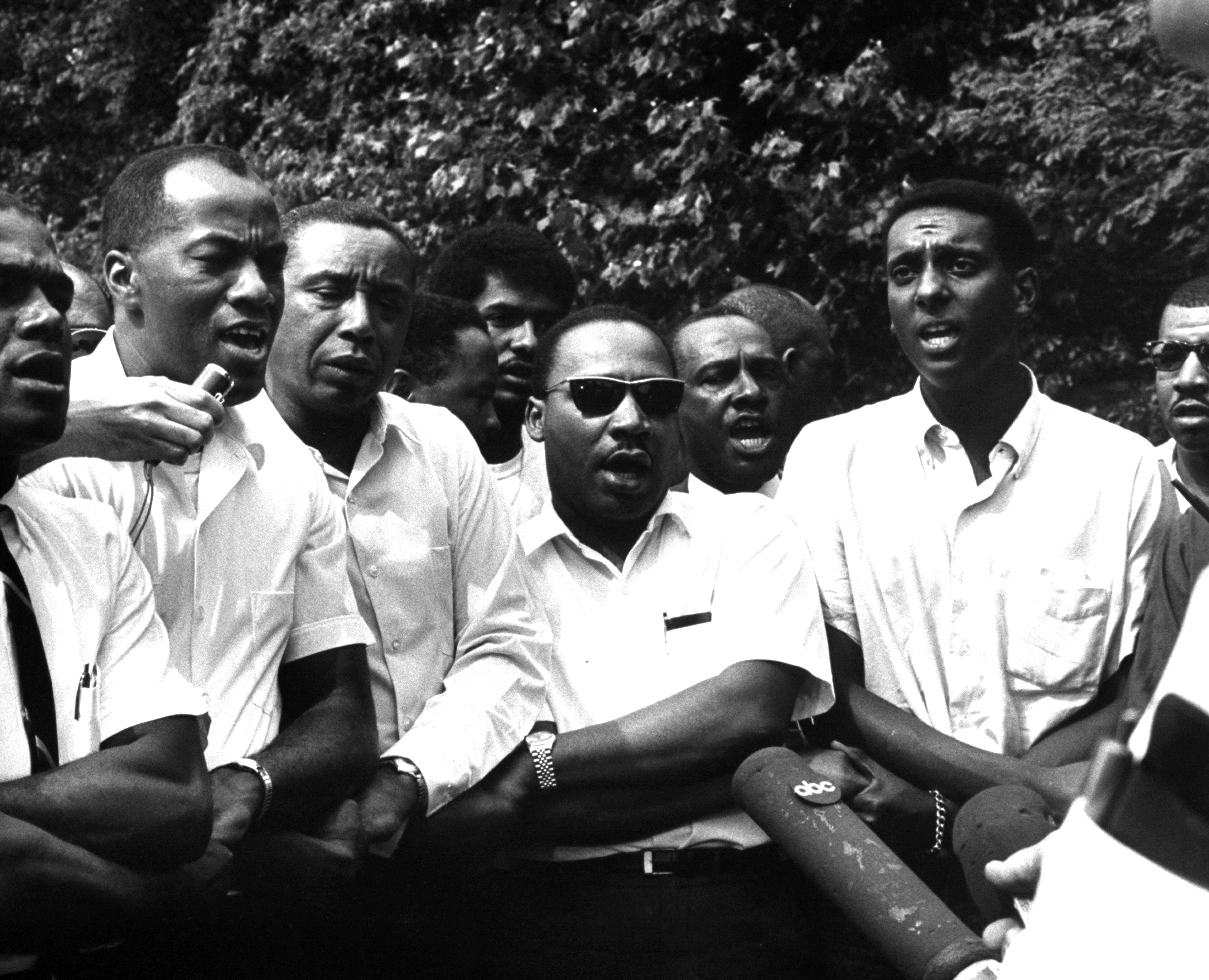Civil rights leaders Floyd B. McKissick (fore, 3L), Dr. Martin Luther King Jr. (4R) and Stokely Carmichael (2R) participating in voter registration march after originator James H. Meredith was shot, 1966.