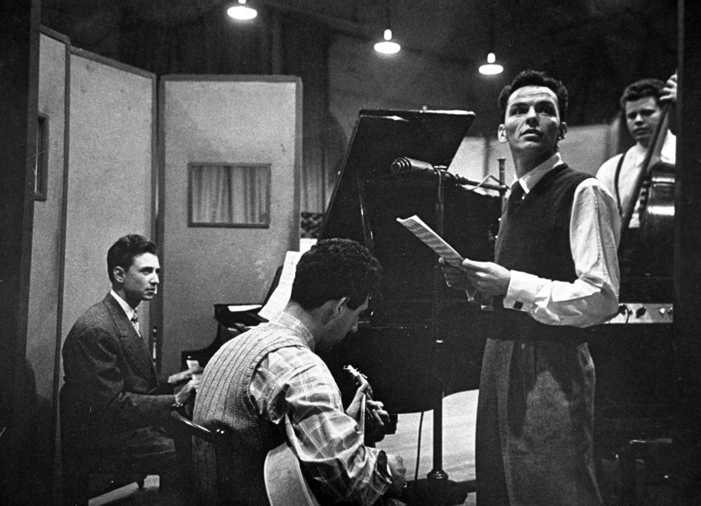 Frank Sinatra and musicians in studio during recording session at CBS.