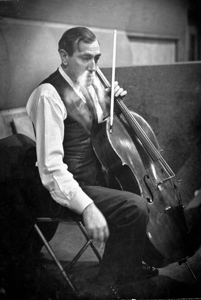 Gregor Piatigorsky unhappily listens to a movement being played back.